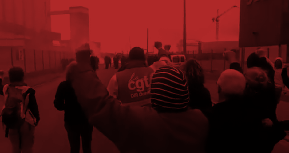 Workers inside a refinery near Marseille/France, with rosen fists, some of them have grey hair. In the background police coming towards them and teargas