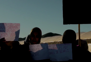 Six women in a desert landscape hold up protest signs